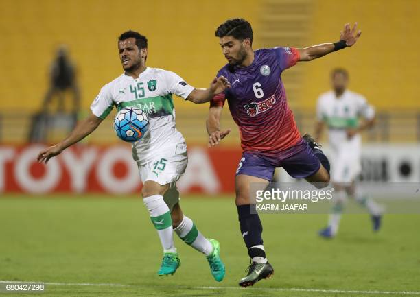 Zob Ahan's Mehdi Mehdipour fights for the ball with alAhli's Abdulfattah Asiri during their Asian Champions League football match between Iran's Zob...