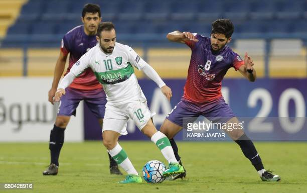 Zob Ahan's Mehdi Mehdipour fights for the ball with alAhli's Ehsan Pahlevan during their Asian Champions League football match between Iran's Zob...