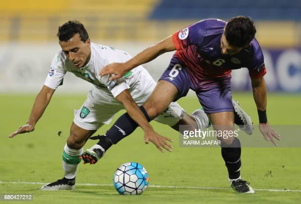 Zob Ahan's Mehdi Mehdipour fights for the ball with alAhli's Mohamed Abdul Shafy during their Asian Champions League football match between Iran's...