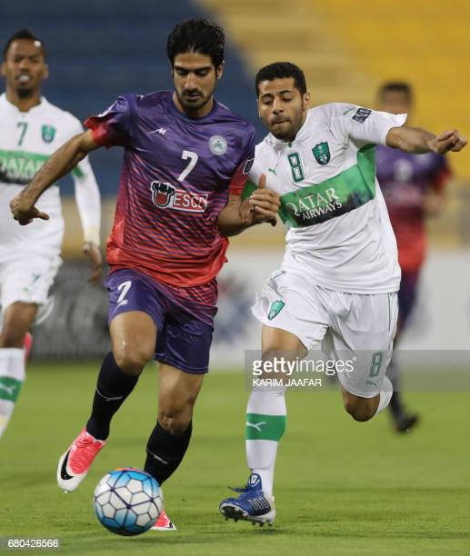 Zob Ahan's Mohammadreza Hossein fights for the ball with alAhli's Taisir Al Jassim during their Asian Champions League football match between Iran's...