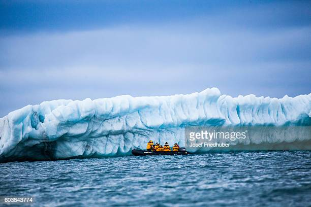 Zodiak with tourists in front of Iceberg arctic ocean