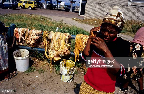 Zohdiwe Mewakbeni talks on her mobile phone while selling cow intestines popular for cooking traditional food at a market October 7 2003 in...