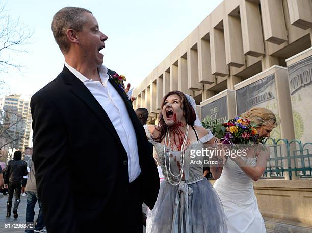 Zombie bride Holly Walker center splits up soon to be married couple William Davis left and his bride Jocelyn right on the 16th St Mall during the...