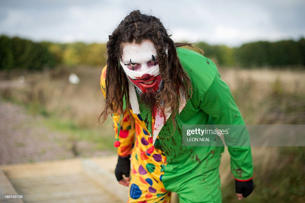 A zombie clown prepares for the runners as he takes part in one of Britain's biggest horror events, the 'Zombie Evacuation Race' at Carver Barracks near Saffron Walden, England, on October 5, 2013. The race sees thousands of participants attempt to complete a gruelling 5 kilometre cross-country run, while evading 'zombies', intent on snatching the three life-line strips hanging from every runner's waist. Those who manage to get through with any strips remaining are named as survivors while those without take home an 'infected' badge. AFP PHOTO/Leon Neal