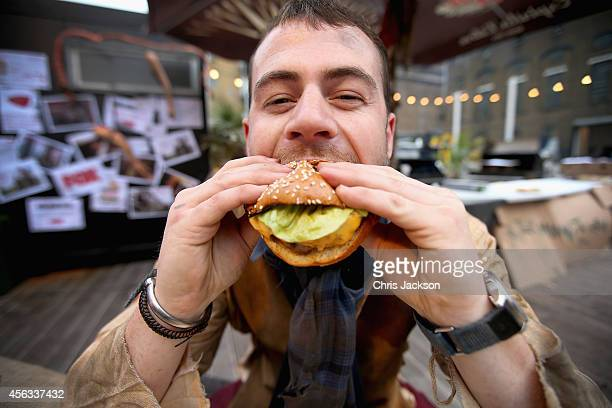 A 'Zombie' member of staff bites into a burger during a photocall to launch 'human flesh' tasting burgers to coincide with the launch of Season 5 of...