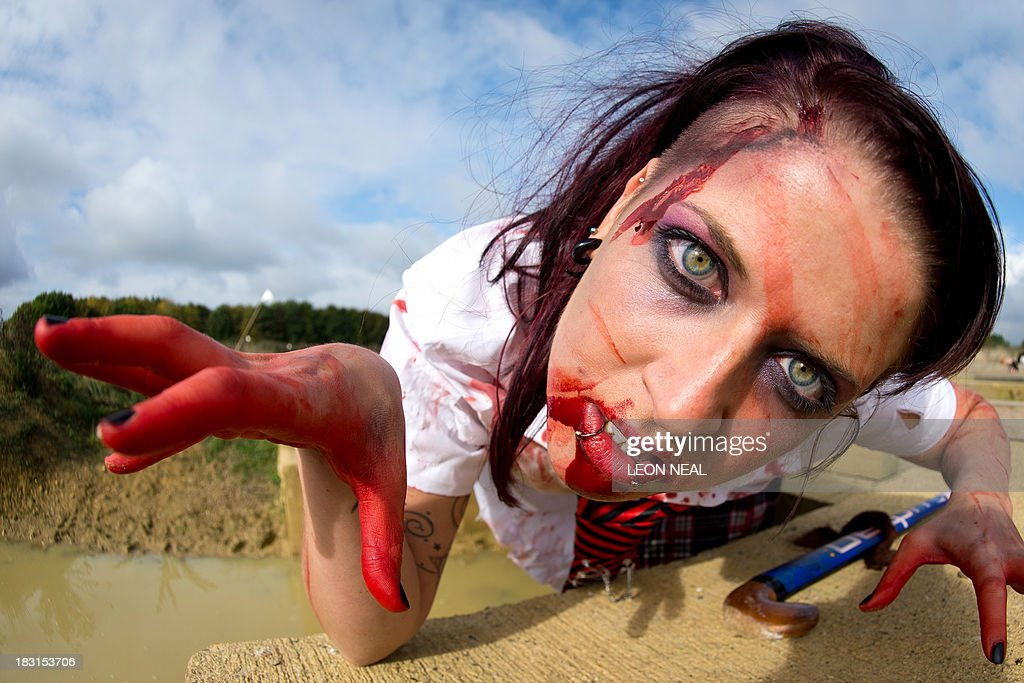 A zombie school girl poses for a picture as she prepares to take part in one of Britain's biggest horror events, the 'Zombie Evacuation Race' at Carver Barracks near Saffron Walden, England, on October 5, 2013. The race sees thousands of participants attempt to complete a gruelling 5 kilometre cross-country run, while evading 'zombies', intent on snatching the three life-line strips hanging from every runner's waist. Those who manage to get through with any strips remaining are named as survivors while those without take home an 'infected' badge. AFP PHOTO/Leon Neal