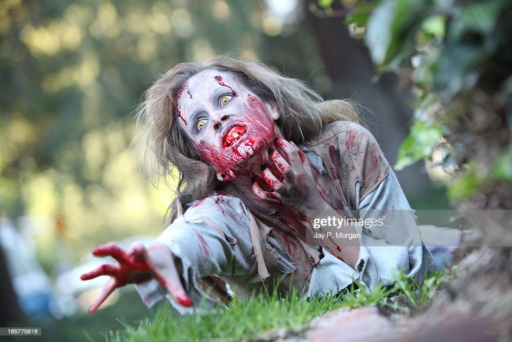 Zombie woman on the grass lawn reaches forward : Stock Photo