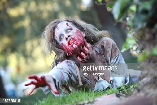 Zombie woman on the grass lawn reaches forward : Foto stock