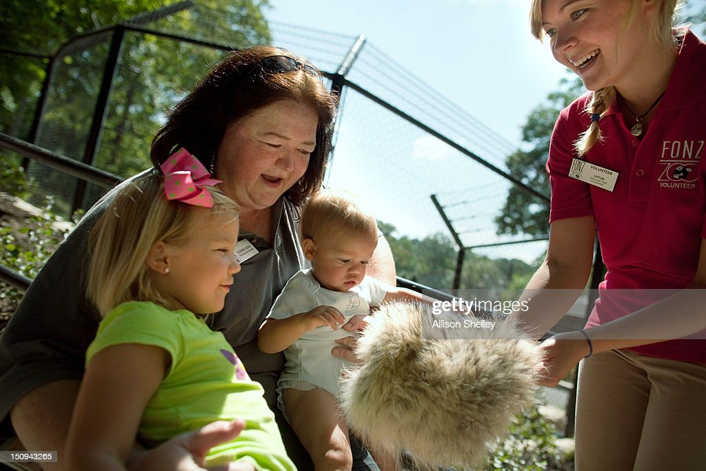 Zoo volunteer Caitlin Arlotta (R) shows a gray wolf pelt to Suzanne Hough, FONZ (Friends of the National Zoo) program supervisor, and her niece Elena Schultz (L) and nephew Derek, 9-months, during a sneak peak of the new American Trail at the Smithsonian National Zoo August 29, 2012 in Washington, D.C. The trail, featuring animals and horticulture native to the Americas, opens to the public on September 1.
