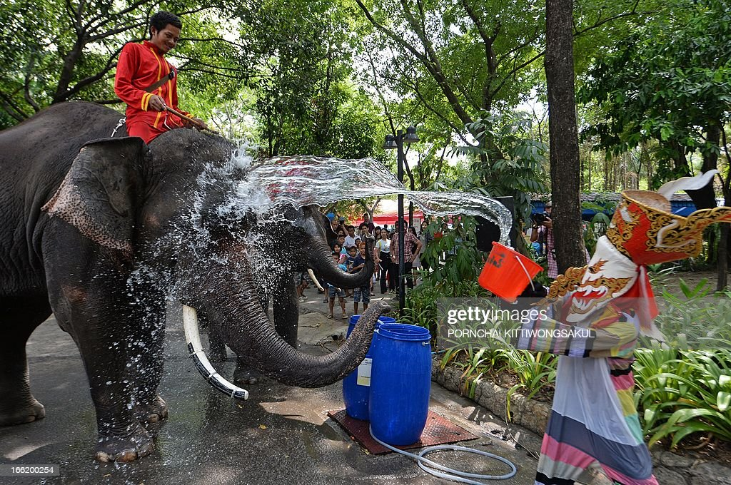 A zoo worker (R) dresses in traditional costume throws water on elephants to promote the Songkran festival at Dusit Zoo in Bangkok on April 10, 2013. Songkran is the Thai New Year which starts on April 13 during which people celebrate by splashing water over each other.