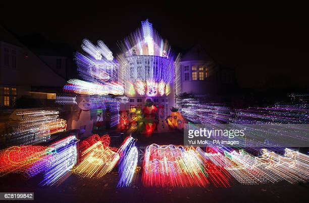 A zoom burst photograph of a residential house decorated with Christmas lights and festive cartoon figures in Highgate north London