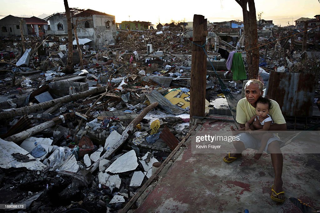Zosimo Moabando sits with his young grandson Kyle on the roof of their damaged house in the devastated town of Tanuan south of Tacloban on November...