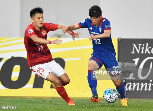 Zou Zheng of Guangzhou Evergrande competes for the ball with Jang Hoik of Suwon Samsung Bluewings during their AFC Champions League group stage...