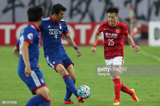 Zou Zheng of Guangzhou Evergrande in action against Park Gidong of Suwon Samsung Bluewings during the AFC Champions League Group G match between...