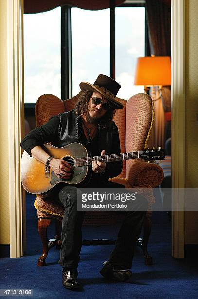Zucchero pseudonym of Adelmo Fornaciari famous Italian singer posing for a photo shoot in a hotel room sitting on a sofa with his guitar Italy 2007