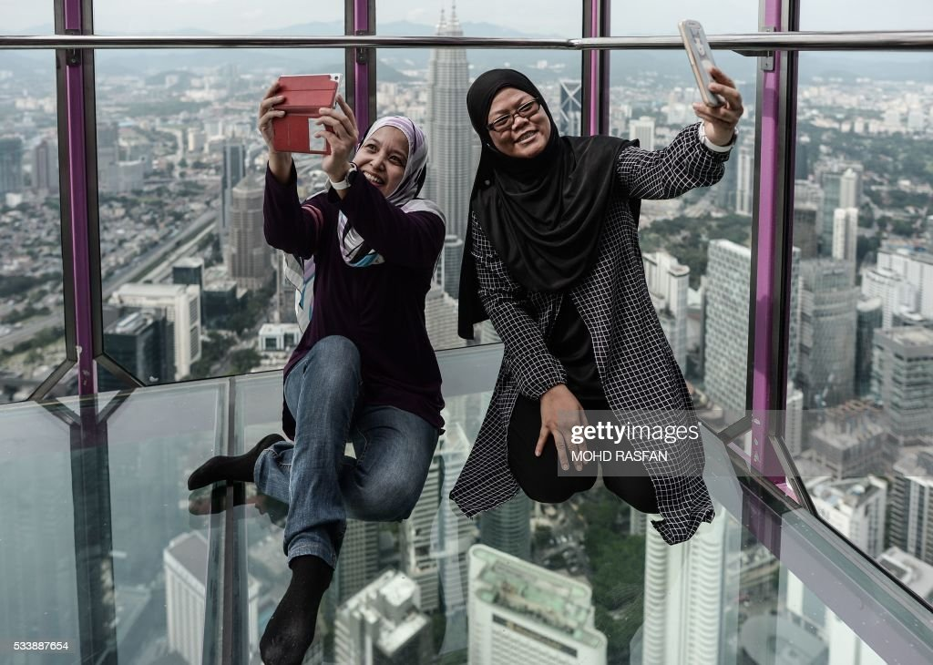 Zurin Holit (R) and Irawati (L) from Malaysia take pictures of the panoramic view of the city from the Sky Box at KL Tower, the world's seventh tallest telecommunications tower, in Kuala Lumpur on May 24, 2016. Officially opened on May 20, the Sky Box has been the latest attraction for tourists arriving to the Malaysian capital. It stands 300 metres above ground and can fit six people at any one time, and offers spectacular views of the Kuala Lumpur skyline, including the iconic Petronas Twin Towers. / AFP / MOHD