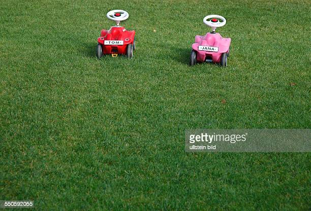 Zwei Bobbycars auf einer Wiese