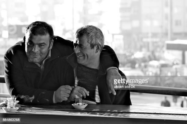 Zwei Freunde auf Fährschiff umarmen sich und lachen