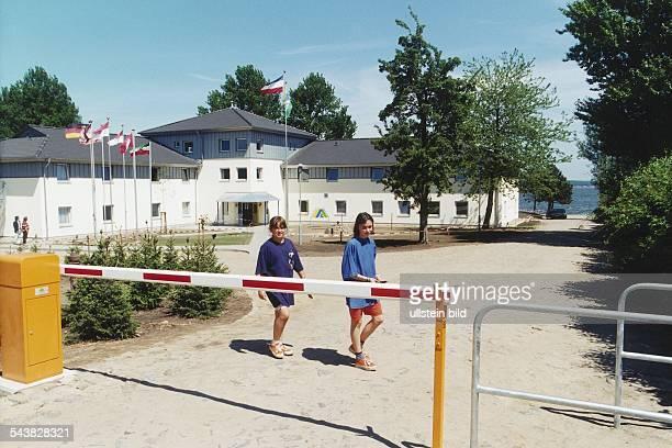 Zwei Mädchen stehen hinter einer Schranke die die Zufahrt zur Jugendherberge Borgwedel versperrt An der Seite des Gebäudes verläuft ein Sandweg zum...
