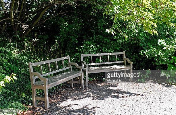 Zwei rustikale hölzerne Gartenbänke an einem Schattenplatz laden zum Verweilen ein