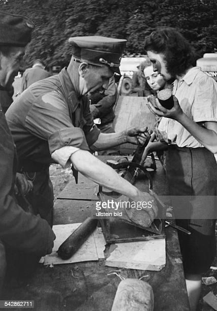 Zweiter Weltkrieg Flüchtlingsversorgung Hamburg Moorweide 3171943 Ein offizieller Helfer portioniert Brot und Wurstrationen um sie an Flüchtlinge zu...