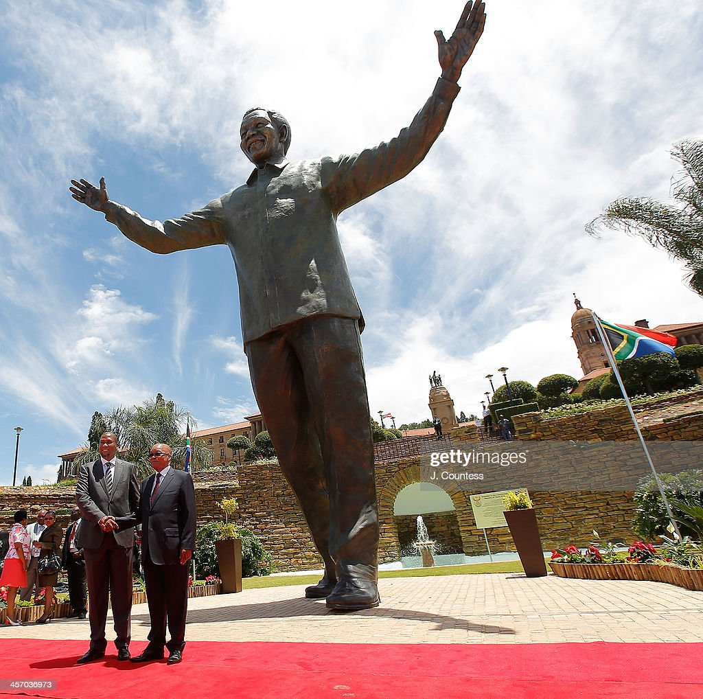 Zwelivelile 'Mandla' Mandela and South African President Jacob Zuma pose for a photo in front of a statue of former South African President Nelson Mandela at the Union Buildings on December 16, 2013 in Pretoria, South Africa. The statue was unveiled on the day after the burial of Nelson Mandela in his home village of Qunu on December 15, 2013. Nelson Mandela passed away on the evening of December 5, 2013 at his home in Houghton at the age of 95. Mandela became South Africa's first black president in 1994 after spending 27 years in jail for his activism against apartheid in a racially-divided South Africa. December 16 is celebrated in South Africa as Reconciliation Day and marks several significant events in South African history.