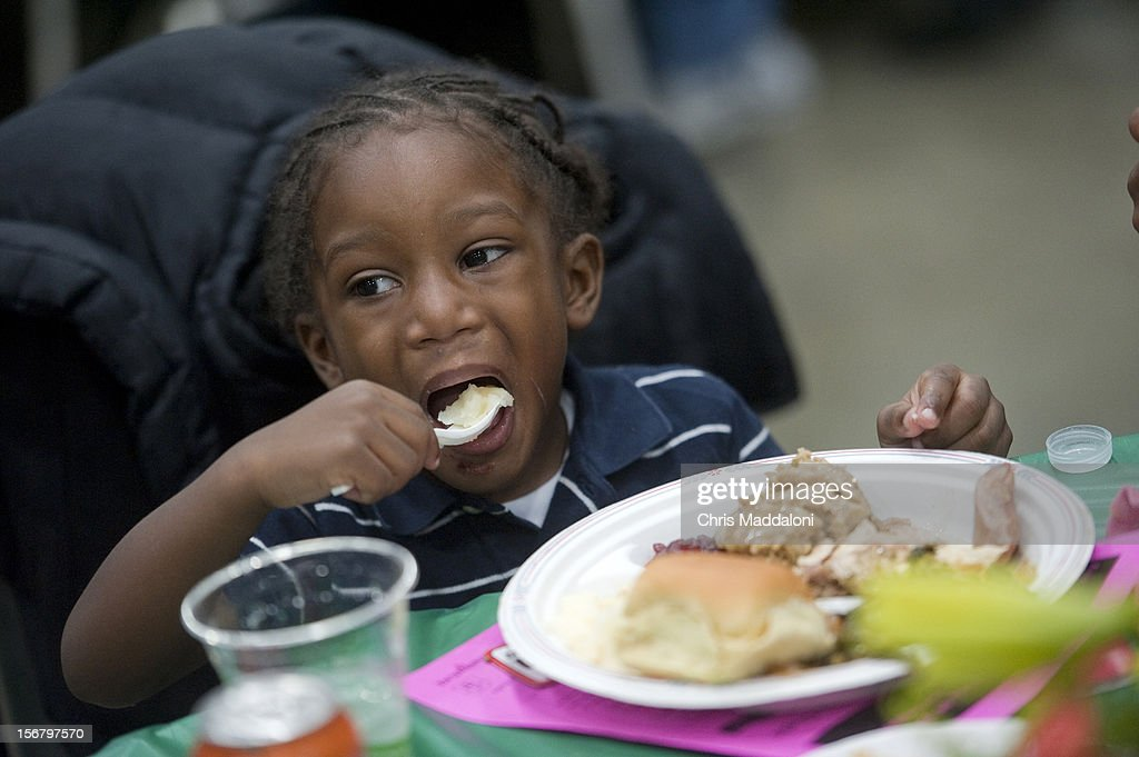 Zyron Howard, 3, from Washington, D.C., enjoys his potatoes at the 13th annual Safeway Feast of Sharing at the Washington Convention Center. More than 5000 people were expected for the free Thanksgiving meal, job and health fair.