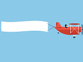 Airplane with blank poster. Plane with banner. Red Biplane with white ribbon in blue sky. Vector