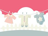 A cartoon vector illustration of cute baby clothings on a washing line.