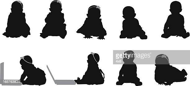 Baby silhouettes sitting up using laptop computer