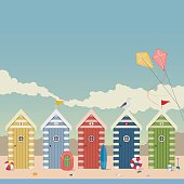 Beach scene with pretty beach huts, a seagull, and kites.
