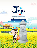 Beautiful Korean Island, Jeju. Yellow rape flower field and stone grandfather. A traditional female diver welcomes you to visit Jeju Island.