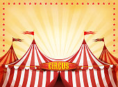 Illustration of cartoon white and red big top circus tents background, with marquee or banner on a yellow summer sky background