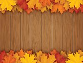 Border from fallen maple leaves on the background of a wooden vintage table surface. Realistic vector illustration.