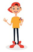Boy in cap holding spinner. Cute cartoon character. Vector illustration.