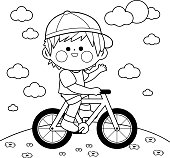 Happy little boy riding a bicycle at the park. Vector black and white coloring book page