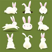 A collection of 9 white bunnies isolated on green 'grass'.
