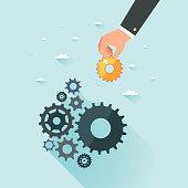 Business development concept. Businessman hand putting gold gear to cogwheel mechanism. Cogwheels as symbol of successful business. Vector illustration.