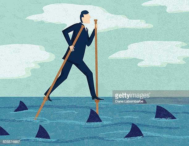Hombre de negocios sobre pilares con tiburones: Peligroso concepto de negocios