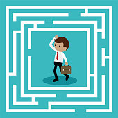 Businessman standing in center of the maze find way out