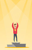 Young caucasian man standing with a gold medal and raised hands on the winners podium. Sportsman celebrating on the winners podium. Winner concept. Vector flat design illustration. Vertical layout.
