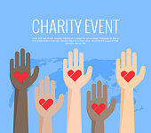 Charity event, hands raised in different colors, heart in the palm of your hand