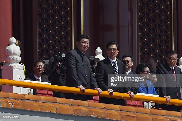 Chinese President Xi Jinping talks with former president Hu Jintao on top of Tiananmen Gate to watch a military parade to commemorate the 70th...