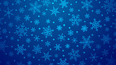 Christmas illustration with various small snowflakes on gradient background in blue colors