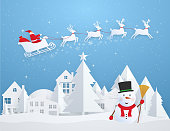 Christmas card with Santa Claus flying over city and snowman. Happy New Year and Christmas, blue winter snowy background in paper style.