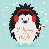 Vector cartoon style Christmas and New Year greeting card with cute hedgehog holding candy cane. Be Merry and Bright text.