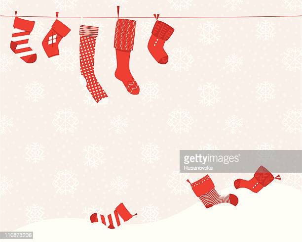 A Christmas setting of red stockings on a line and in snow