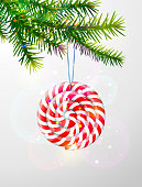 Striped peppermint lollipop hanging on pine twig. Best vector image for christmas, new years day, decoration, winter holiday, sweet-stuff, new years eve, etc