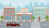 City life illustration with house facades, road and other urban details. Flat style, vector.
