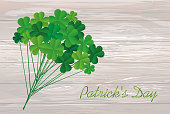 Clover bouquet on sticks. Greeting otkryka on St. Patrick's Day. Irish holiday. Free space for your text or advertisement. Vector illustration on a wooden background.
